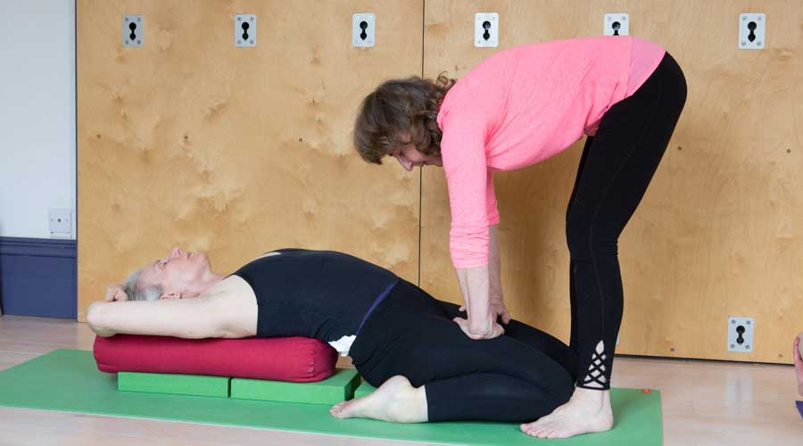 Barbara Norvell Iyengar yoga teacher adjusts a student in Supta Virasana