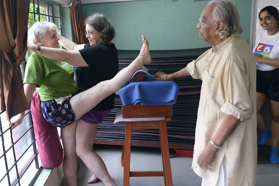 Stephanie adjusts a student overseen by BKS Iyengar and his granddaughter Abhijata at Ramamani Iyengar Memorial Yoga Institute (RIMYI) in Pune.